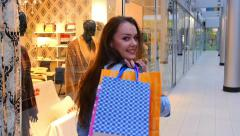 Beautiful girls with shopping bags goes on shopping center. Slow motion. - stock footage