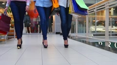 Three beautiful girls with shopping bags goes on shopping center. Slow motion. - stock footage