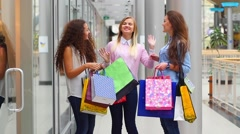 Three beautiful girls with shopping bags watch purchase on shopping center. Slow - stock footage