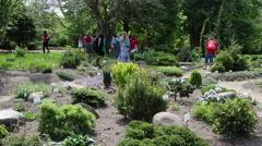 People walk between various species plants with names in garden Stock Footage