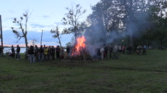 People surrounded big fireplace nea lake in evening light Stock Footage