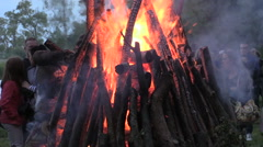 Zoom out of pfire stacked burning log and landscape with people Stock Footage