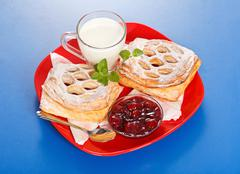 breakfast: two sour cherry cakes, milk and jam on plate - stock photo