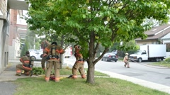 Firemen donning masks and preparing fire attack with smoke showing Stock Footage