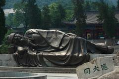 statue of sleeping sage on the entrance to Huangshan park - stock photo