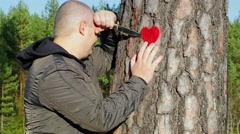 Sorrowful man holding knife and fabric heart near the tree - stock footage