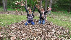 4k two teens  throw autumn leaves,  sony steadycam shoot, stock video Stock Footage