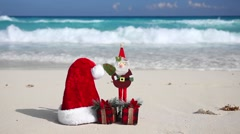 Christmas Helper Hat, Santa Claus toy and present box on beach Stock Footage