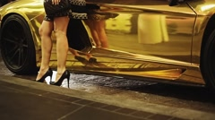 Gold car with Woman's Bare Legs in Heels standing in front Stock Footage