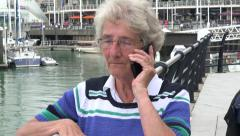 senior woman makes telephone call outside on cell phone - stock footage