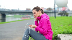 Female jogger resting and listening to the music in the city HD Stock Footage