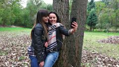 4k smartphone selfie photo  by two happy teens in autumn park. sony uhd stead Stock Footage