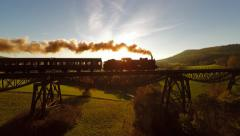 Aerial view of steam engine locomotive crossing bridge at sunset magic hour Stock Footage