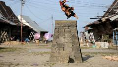 Man in traditional warrior attire stone jumping Stock Footage