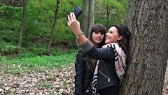 4k two happy girlfriends taking selfie photo with their smartphone in the par - stock footage
