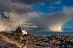 Lighthouse along rocky shore with storm clouds in distance Stock Photos