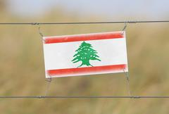 Border fence - old plastic sign with Lebanon flag Stock Photos