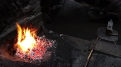 Stock Video Footage of Wrought iron being shaped in the back and a fire burning in the foreground