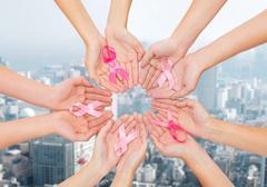 Close up of hands with cancer awareness symbol Stock Photos