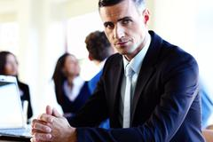 Serious businessman sitting at the table in front of colleagues Stock Photos