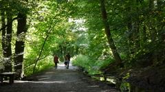 Young family walking through Skipton Castle Woods Stock Footage