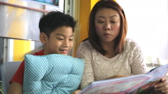Little Asian cute child with mother reading book in library . Stock Footage