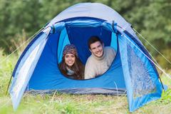 smiling couple of tourists looking out from tent - stock photo