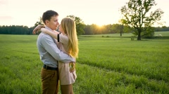 Young loving couple embracing in a field - stock footage