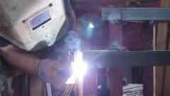 A welder using a protection mask is welding steel construction - stock footage