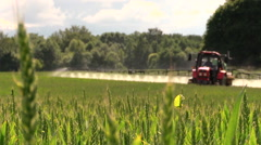 tractor sprayer work in green young cereal field on summer day - stock footage