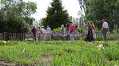 Group of tourists people walk in botanical garden Stock Footage