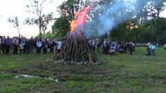 People crowd around burning log campfire on summer evening Stock Footage