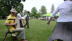 Panorama of man musician play accordion and people dance folk Stock Footage