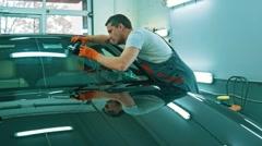 Worker on a car wash applying anti rain coating on a windshield Stock Footage
