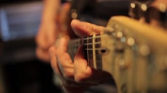 Footage of a man playing on his electric guitar in a recording studio - stock footage