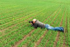man lying on green field and photographs - stock photo