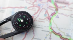 Somebody puts a compass on a road map to discover where the right road is - stock footage