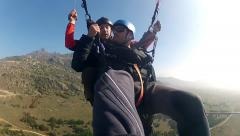 Paragliding over mountains against clear blue sky Stock Footage