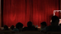Stock Video Footage of red stage curtains and blurred audience in the theater