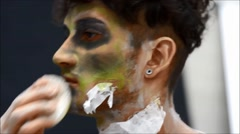 Young male actor or performer applying zombie make-up on his face Stock Footage