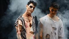 Two scary male zombies dancing a silly dance in studio Stock Footage