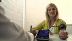 Stock Video Footage of Woman getting blood pressure checked by doctor - dolly
