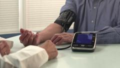 Man getting blood pressure checked by doctor - close, dolly - stock footage