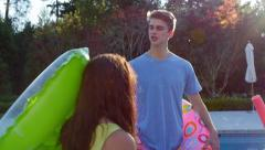 Teens Hang Out At Pool, Girl Steals Her Friend's Pool Toy, Her Friend Chases Her Stock Footage
