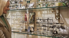 Pan shot of mature couple in shop looking at jewellery Stock Footage
