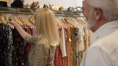 Mature couple in shop looking at dresses Stock Footage
