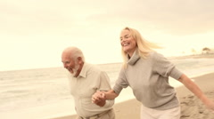 Mature couple running on beach Stock Footage