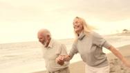 Mature couple running on beach - stock footage
