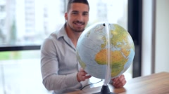 young man spinning globe and smiling - stock footage
