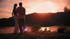 Pan shot of couple standing in park overlooking lake in sunset - stock footage